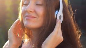 Die Frau, die Musik in den Kopfhörern mit Augen hört, schloss auf dem im Freien Porträt eines schönen Nahaufnahmemädchens stock video