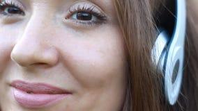 Die Frau, die Musik in den Kopfhörern mit Augen hört, schloss auf dem im Freien Portrait einer schönen Mädchennahaufnahme stock footage