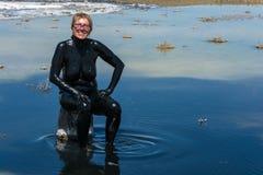 Die Frau nimmt die heilenden Schlammbäder auf dem See Baskunchak an Stockfotografie