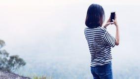 Die Frau, die pflegt, ein Fototelefon zu nehmen, das Konzept der Anwendung des Telefons, ist im Alltagsleben wesentlich stockfotografie