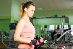 Die Frau rüttelt ihre Muskeln auf dem Simulator in der Turnhalle Stockfoto