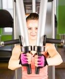 Die Frau rüttelt ihre Muskeln auf dem Simulator in der Turnhalle Stockbilder