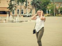 Die Frau richtet ihr Haar auf dem Hintergrund der alten Stadt gerade Lizenzfreie Stockfotos