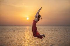 Die Frau schönes Schattenbild gegen das Meer und die Dämmerung springend Lizenzfreie Stockbilder