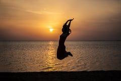 Die Frau schönes Schattenbild gegen das Meer und die Dämmerung springend Stockbilder