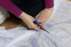 Die Frau schneidet das Gewebe mit Scheren für nähende Vorhänge auf dem Fenster Das Gewebe liegt auf dem Boden Ansicht von oben Stockfotografie