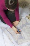 Die Frau schneidet das Gewebe mit Scheren für nähende Vorhänge auf dem Fenster Das Gewebe liegt auf dem Boden Ansicht von oben Lizenzfreie Stockbilder
