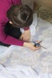 Die Frau schneidet das Gewebe mit Scheren für nähende Vorhänge auf dem Fenster Das Gewebe liegt auf dem Boden Ansicht von oben Lizenzfreies Stockbild