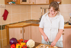 Die Frau schneidet Pilze Stockfoto
