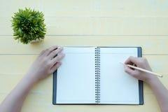 Die Frau schrieb das Buch mit einem Lehmbuch in einen gelben Hintergrund Die Draufsicht stockfotografie