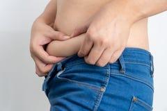 Die Frau, die seinen fetten Bauch berührt, hat Übergewicht stockfotos