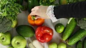 Die Frau setzt die Pfeffer auf dem Tisch mit grünem Gemüse stock footage