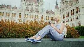 Die Frau sitzt auf dem Hintergrund des ungarischen Parlaments, benutzt einen Smartphone Tourismus in Europa, ausgezeichnetes Buda stock video