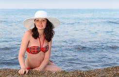 Die Frau sitzt auf Seeküste Lizenzfreie Stockbilder