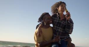Die Frau, die an sitzt, bemannt Schoss am Strand 4k stock video