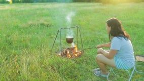 Die Frau sitzt durch das Feuer, über dem der Werfer, der Kohlen hängt und rührt Geschossen von der Seite stock footage