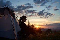 Die Frau sitzt im Zelt an der Spitze des Berges den Sonnenuntergang genießend auf unscharfen Hintergrundhügeln Lizenzfreies Stockfoto