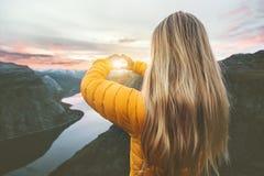 Die Frau, die in Sonnenuntergangberge reist, übergibt das geformte Herzsymbol stockfotos