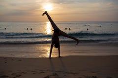 Die Frau, die Spaß am Strand gegen den Sonnenuntergang springt und hat stockfotografie