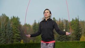 Die Frau springend auf das Springseil im Herbstpark stock video