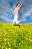 Die Frau springend auf dem Gebiet Lizenzfreie Stockfotos
