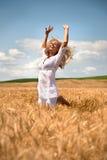 Die Frau springend auf dem Weizengebiet Stockfotografie