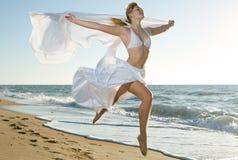 Die Frau springend auf den Strand Lizenzfreie Stockfotografie