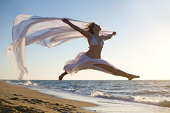 Die Frau springend auf den Strand Lizenzfreie Stockbilder