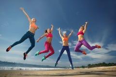 Die Frau springend auf den Strand Stockfotografie