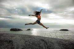 Die Frau springend auf einen Felsen bei Sonnenuntergang auf Bakovern-Strand, Cape Town lizenzfreie stockbilder
