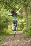 Die Frau springend auf Pfad Lizenzfreies Stockbild