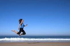 Die Frau springend in den Strand Lizenzfreie Stockbilder