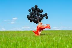 Die Frau springend mit schwarzen Ballonen in den Händen Lizenzfreies Stockbild