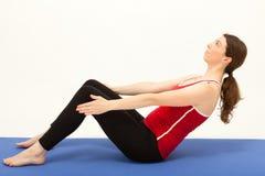 Die Frau trainiert auf einer Matte Stockfoto