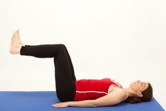 Die Frau trainiert auf einer Matte Stockbild