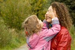 Die Frau und Mädchen, die im Garten spielen, Mädchen schließt Augen Stockfotos