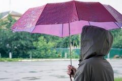 Die Frau unter dem Regenschirm versteckt sich vom Regen Regen auf a Lizenzfreie Stockfotos