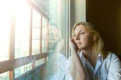 Die Frau verlor im Gedanken, der heraus das Fenster schaut Stockbilder
