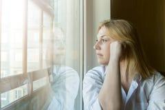 Die Frau verlor im Gedanken, der heraus das Fenster schaut Lizenzfreies Stockfoto