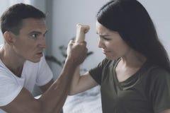 Die Frau versuchte, den Mann zu schlagen, der nahe bei ihr saß, aber er fing sie ab und drückte ihre Hand zusammen stockfoto