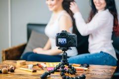 Die Frau, die Video für ihr Blog auf Kosmetik unter Verwendung des Stativs herstellt, brachte Digitalkamera an Stockfotos