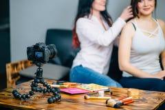 Die Frau, die Video für ihr Blog auf Kosmetik unter Verwendung des Stativs herstellt, brachte Digitalkamera an Stockfoto