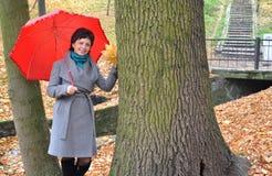 Die Frau von durchschnittlichen Jahren kostet unter einem roten Regenschirm im Herbstpark Stockfotografie