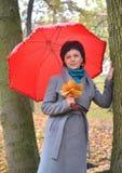 Die Frau von durchschnittlichen Jahren kostet unter einem roten Regenschirm im Herbstpark Stockfotos