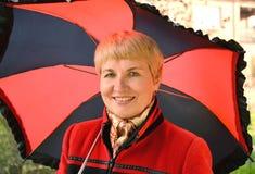 Die Frau von durchschnittlichen Jahren kostet unter einem schwarz-roten Regenschirm Stockfoto