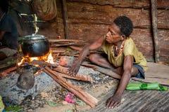 Die Frau von einem Papuanstamm korowai kocht Lebensmittel Korowai Kombai (Kolufo) Stockbilder