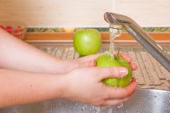 Die Frau wäscht einen grünen Apfel Lizenzfreies Stockfoto