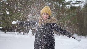 Die Frau wirft etwas Schnee in der Luft die kalte Jahreszeit genießend stock video
