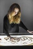 Die Frau zeichnet auf Sand, Sandanimation, Sand gießt aus seinen Händen Lizenzfreies Stockbild