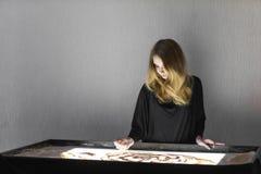 Die Frau zeichnet auf Sand, Sandanimation, Sand gießt aus seinen Händen Lizenzfreie Stockfotografie